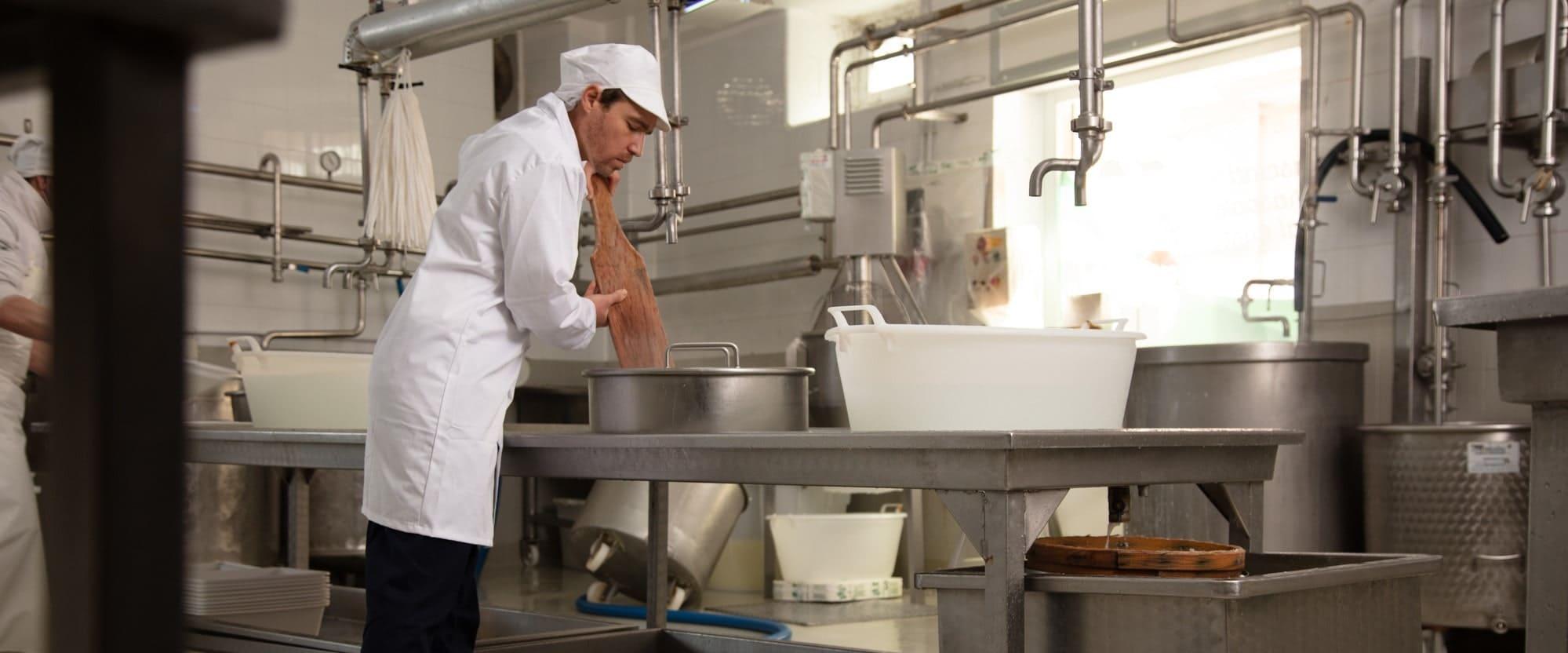 Labor mit unterschiedlichen Edelstahlamaturen, im Zentrum steht ein Mann im weißen Laborkittel mit einem Holzspatel in der Hand.