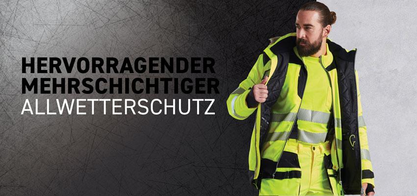 Bärtiger Mann in mehrschichtiger Allwetter-Warnschutzkleidung.