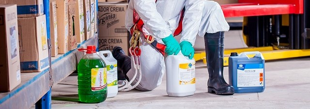 Person in weißem Schutzanzug mit Handschuhen und Sicherheits-Gummistiefeln bei der Arbeit mit Chemikalien.