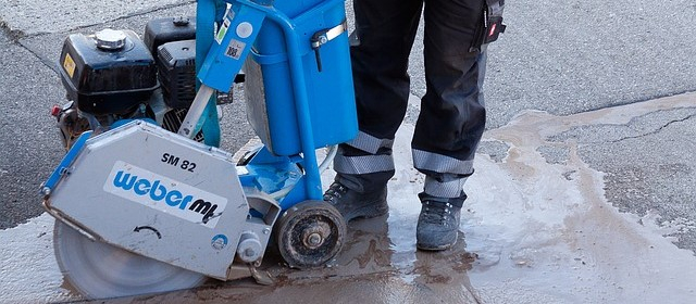 Arbeiter in Warnschutzhose mit Sicherheitsschuhen im Straßenbau.