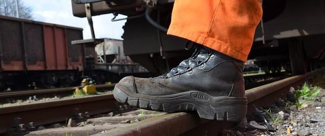 Arbeiter mit Warnhose in Orange und Arbeitsschuhen.